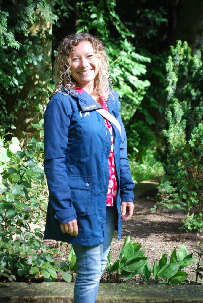 smilende pige i blåjakke midt i en have